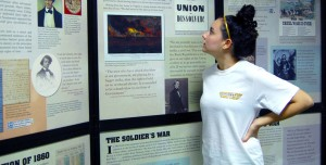 "Sophomore Kendra Mitchell reads over the ""Defining Liberty"" exhibit displayed on the first floor of the Cook Library. Susan Broadbridge/Printz"