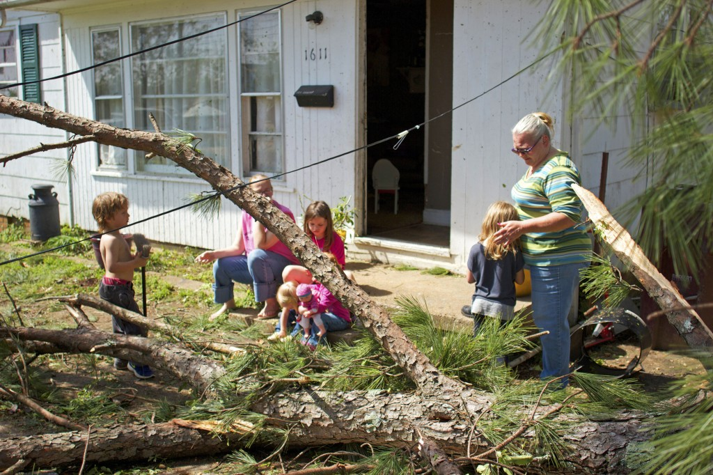Kim Linych and her neices and nephew sit outside, grieving the destruction from the dangerous storm system that killed nine people in Mississippi and several others in neighboring states. Tupelo, the hometown of Elvis Presley, tallied one of the total 31 deaths resulting from the Monday night twisters. Bart Aguirre, the Tupelo chief of police, said emergency crews will have their hands full this week. These crews began their work Tuesday morning by going door to door, searching for both the living and the dead.  Hunt Mercier/Printz