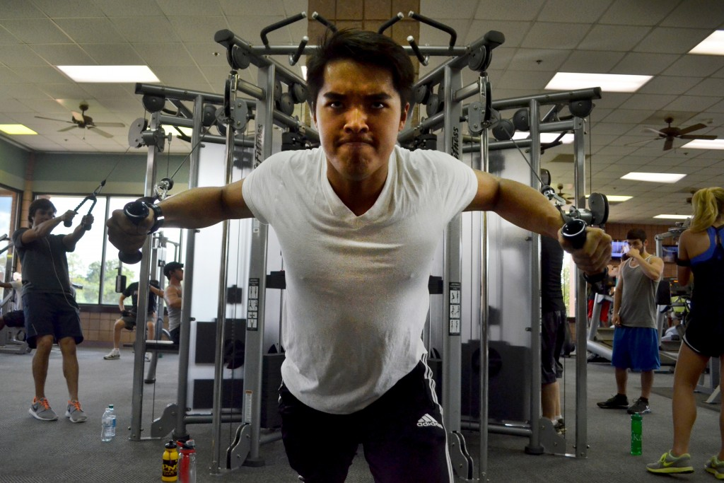 Junior Ryan Vo pumps out his last few reps at the Payne Center as he works on his gym etiquette Tuesday afternoon.   Photo by Aaron J. Stewart