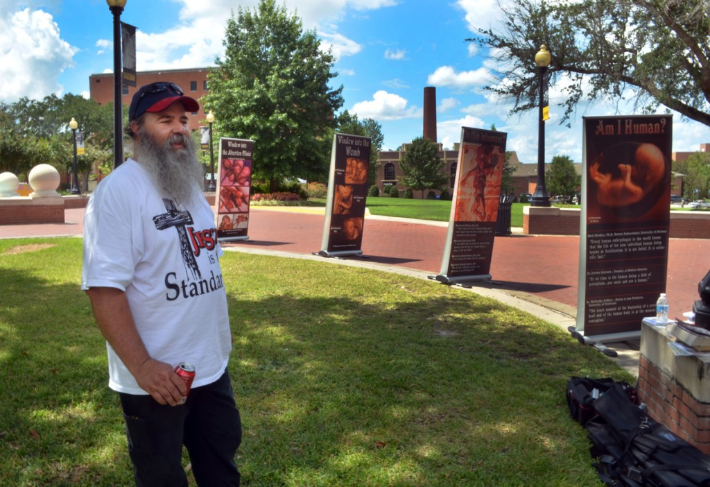 Pro-life protestor Johnny Brekeen stands amongst the anti-abortion signs being displayed on the USM campus near the fountain on Tuesday afternoon. | Photo by A.J. Stewart