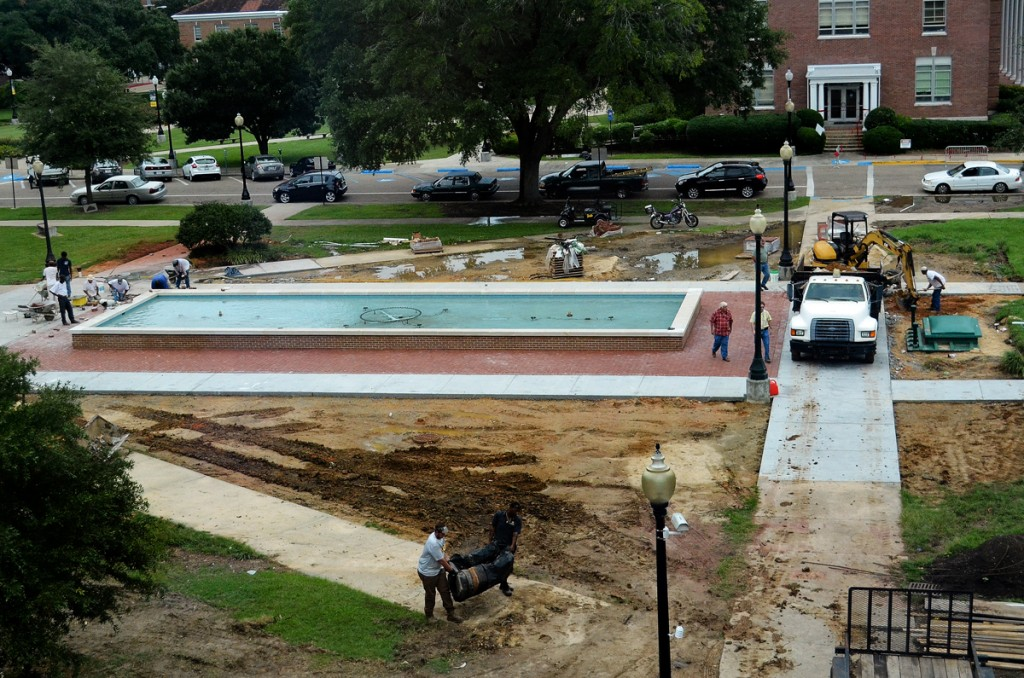 Construction workers take down the fence surrounding the fountain in front of the Administration Building Tuesday afternoon. Rennovations of the area are in progress as water is added to the fountain and the landscape is being improved. | Photo by Susan Broadbridge