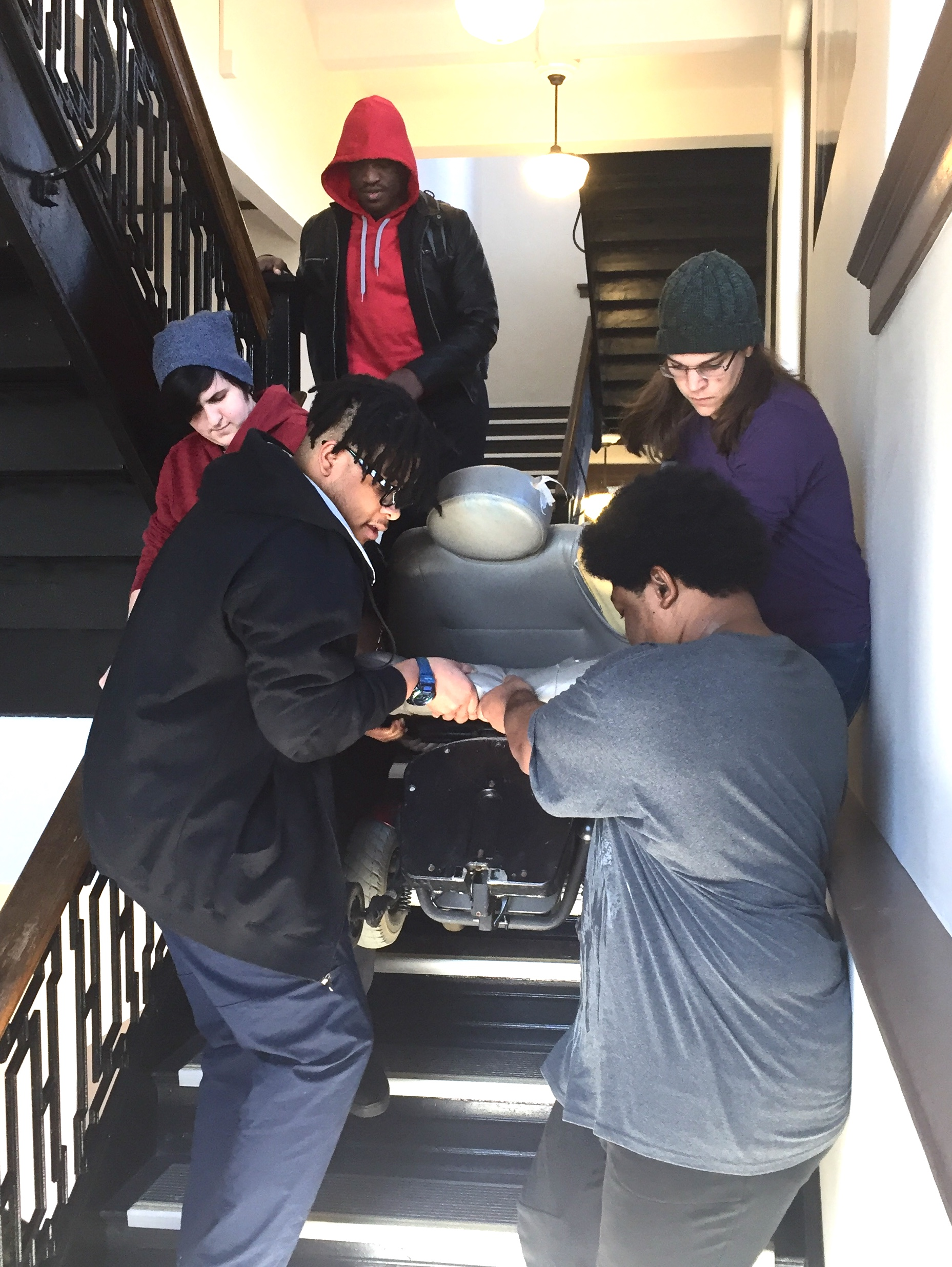 Students carry classmate's wheelchair down three flights of stairs.
